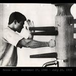 bruce lee doing pak sau punch on wooden dummy.jpg