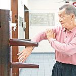 ip ching doing a bong sau technique on a wing chun dummy.jpg